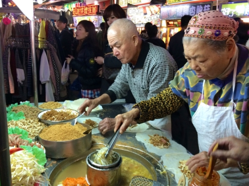 Older couple making spring rolls